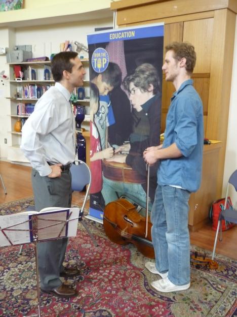 Cellist Sebastian Baverstam speaks with Epiphany School Headmaster John Finley following a From the Top program at the school.