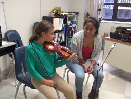 Arts leader Julia Churchill working with CLCS student Margarit on her violin part